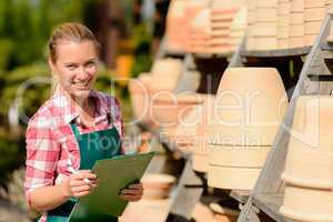 garden center woman standing by clay pots