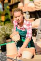 garden center woman putting clay pots cart