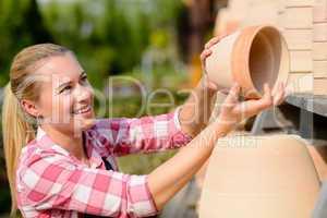 garden center woman putting clay pots shelf