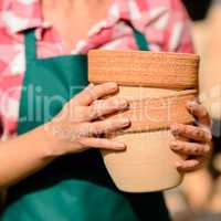 close-up hands holding two clay pots