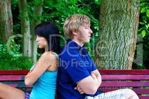 Mann und Frau sitzen Rücken an Rücken auf der Parkbank