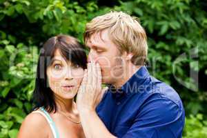 Mann flüstert der Frau ins Ohr