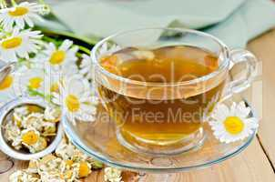 Herbal chamomile tea in cup with strainer on board