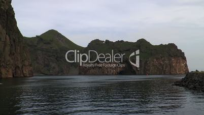 boat passing rocks at westman islands in iceland