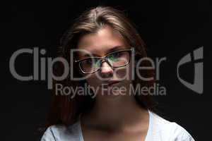 Serious teenager girl in shadow with glasses