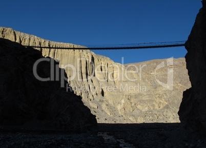 Suspension bridge and limestone cliffs