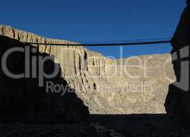 Suspension bridge and limestone cliffs