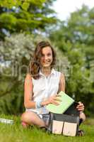 Teenage student woman sitting grass with books
