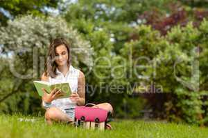Teenage girl reading book sitting in park