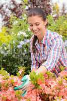 Garden center woman stands in flowerbed smiling