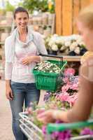 Woman buying flower shopping basket garden center