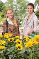 Two woman standing by sunflowers garden center