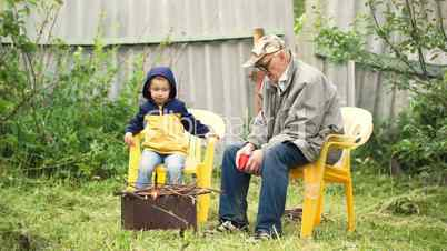 Grandson and grandfather sitting by fire in the yard