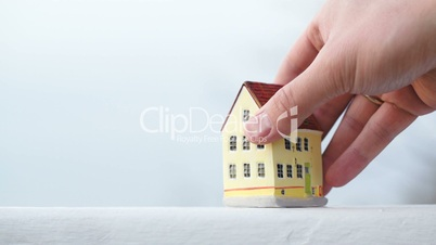 Putting a small toy house on the table