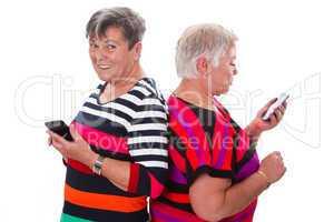 Zwei Seniorinnen kommunizieren per Handy