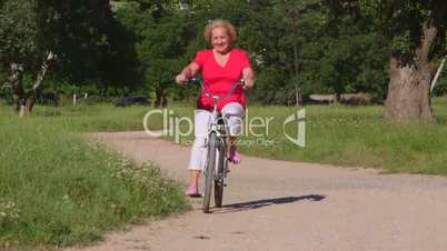 Active senior woman rides bicycle along the path in park