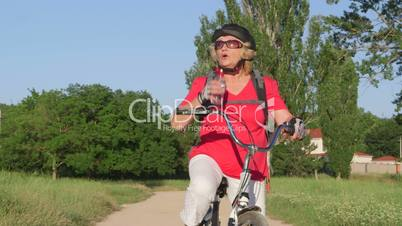 Active senior woman cyclist riding bicycle