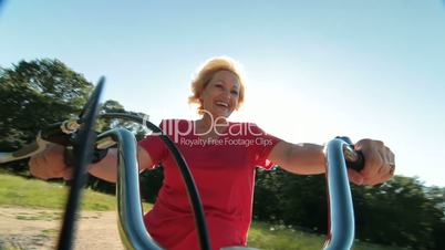 Active senior woman riding bicycle against the sun smiling