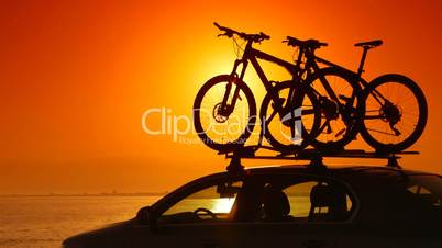 Trip on summer beach by car with mounted bikes at sunset