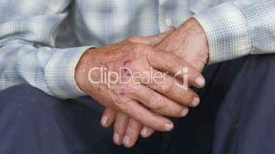Tired scraped hands of elderly farmer