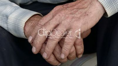 Senior male hands with scraped knuckles and chipped black nails