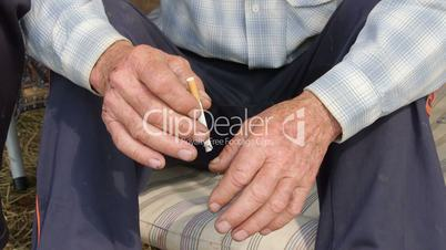 Tired scraped hands of elderly farmer with cigarette