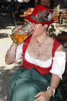Woman in typical bavarian costume drinks beer