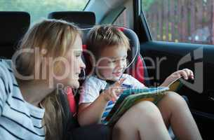 Mother and son with a book in the car