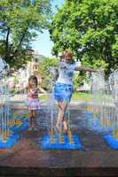 Mother and her daughter playing in the city fountain
