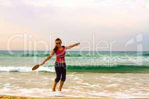 Girl on the beach with a racket.