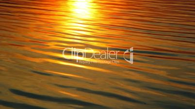 Reflection of the setting sun in the water. Evening landscape. Sunset over the river. Waves on water.