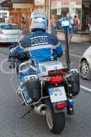 Polizist auf Motorrad, aufgenommen von hinten