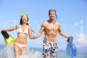 Beach couple fun in water laughing snorkeling