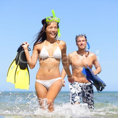 Beach couple having fun on vacation travel snorkel