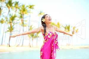Happy woman praising freedom, palm beach in sarong