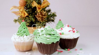 Festive cupcakes with almonds and fruit on a white background.