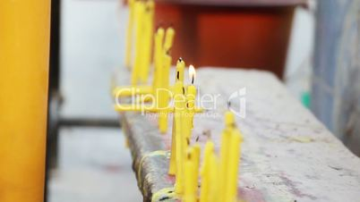 row of candles in buddhistic temple outdoor