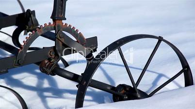 Wheel of an old agri tool stuck on the snow