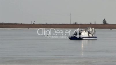 A blue boat on snow moving fast