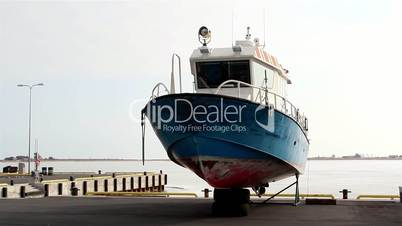 A blue speedboat on standby on the port