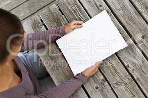 Young woman sitting at wooden table with a booklet with white Cover