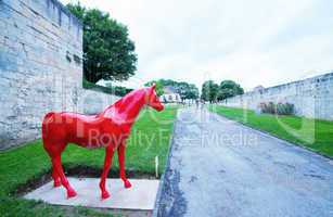 Red horse statue inside Chateau Ducal, a castle in the center of