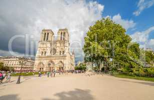 PARIS - JUNE 22, 2014: Tourists enjoy Notre Dame on a sunny day.