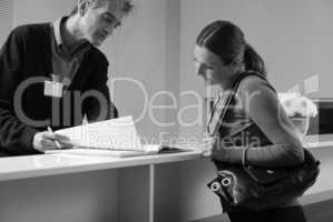 Happy female patient in 40s registering at hospital reception de