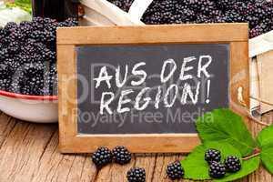 Tafel mit Text: Aus der Region, vor Brombeeren