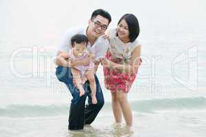 Happy Asian family playing at outdoor sand beach