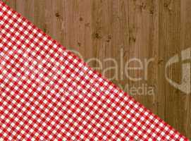 Holztisch mit diagonaler Tischdecke in rot-weiß