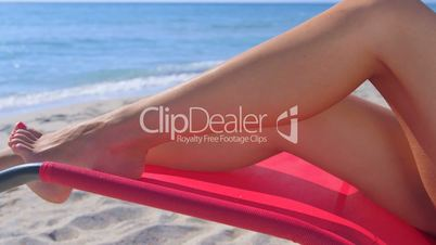 Dolly: Tanned female legs in lounge chair on summer sandy beach