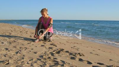 Fitness girl runner lacing footwear before exercising on the beach