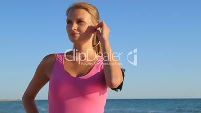 Fitness athletic girl using sport wireless headset while exercising on the beach